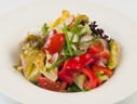 Homemade salad with fresh vegetables and greens in flavorous sunflower oil